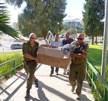 Yad Sarah volunteers carrying medical equipment along walkway to client