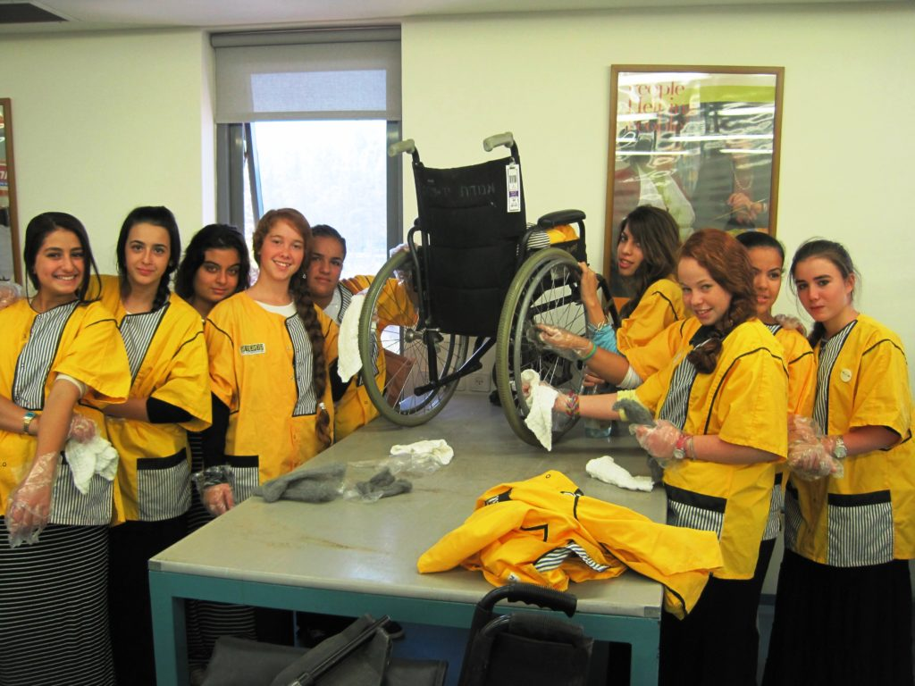 Students at the Visitors' Center in bright yellow aprons learn how to clean wheelchairs after they are returned to Yad Sarah