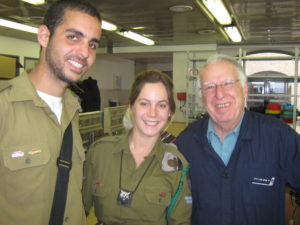 A male and afemale soldier stand beside an older gentleman, all volunteers for Yad Sarah