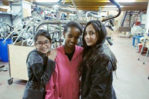 3 girls stand in front of a bin of mobility equipment in a Yad Sarah warehouse. All are Yad Sarah volunteers
