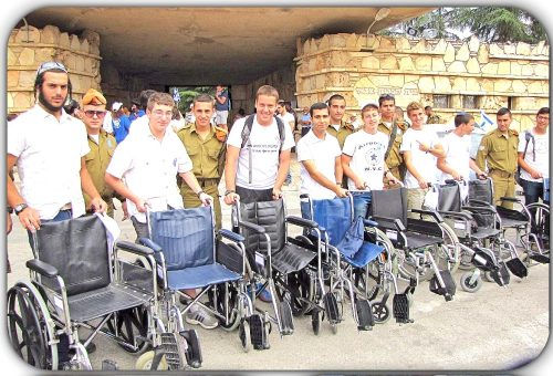 Young volunteers, civilian and soldiers, await behind wheelchairs to assist the disable to get to the polls to vote.