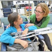 Young girl sitting in wheelchair with crutches lying across the arms of the chair as woman crouches to talk to her