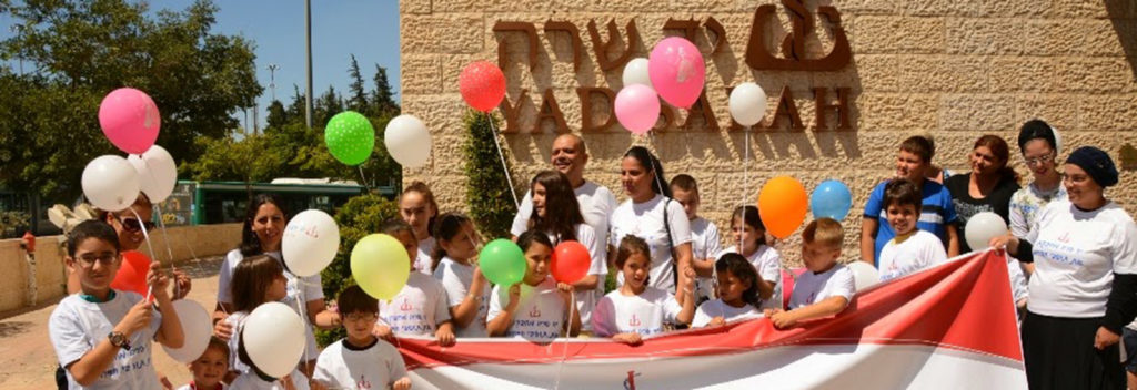 Sderot children standing in front of Yad Sarah House holding balloons and a large Yad Sarah banner in front of the group of children