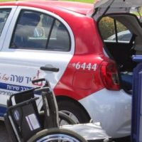 A Yad Sarah hatchback vehicle in bright red, white and blue, hatchback open with driver adjusting specialized bed and wheelchair