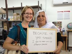 Helen and Rekad hold a sign saying that because of Yad Sarah they get to meet lots of different people