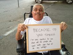 An older Druze gentleman sitting in a wheelchair with an oxygen tube in his nose holds a sign saying he is excited that Yad Sarah is now finally in his village