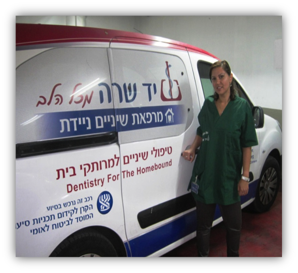 A Yad Sarah special van called Dentistry for the Homebound sits in a garage with a young lady standing at the side waiting to attend clients in their homes.