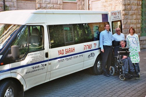 Stephen Hawking in his wheelchair near the rear of the Yad Sarah van and in front of Yad Sarah House
