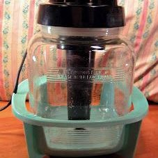 An old glass vaporizer with a black plastic top and a mint green base