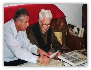 Yad Sarah volunteer sits with a Holocaust survivor and her photo album helping her record her life stories
