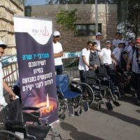 Yad Sarah volunteers stand behind wheelchairs prepared to assist physically disabled reach the gravesites of their lost ones on Memorial Day 2018.