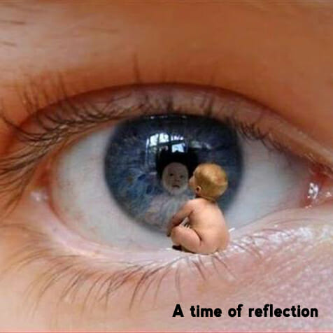 Baby sitting on the bottom eyelid of his larger self with his reflection in the eyeball