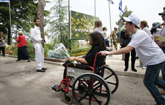 Yad Sarah volunteers help mobility challenged individuals reach graves on Israel's Independence Day.