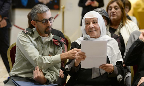 Samira Alaa Abu-Rukun, a Druze volunteer at Yad Sarah sits beside her son, Brig.-Gen. Alaa Abu-Rukun, aide to President Rivlin of Israel. Samira is holding a microphone and making a speech at the 45th anniversary of Yad Sarah