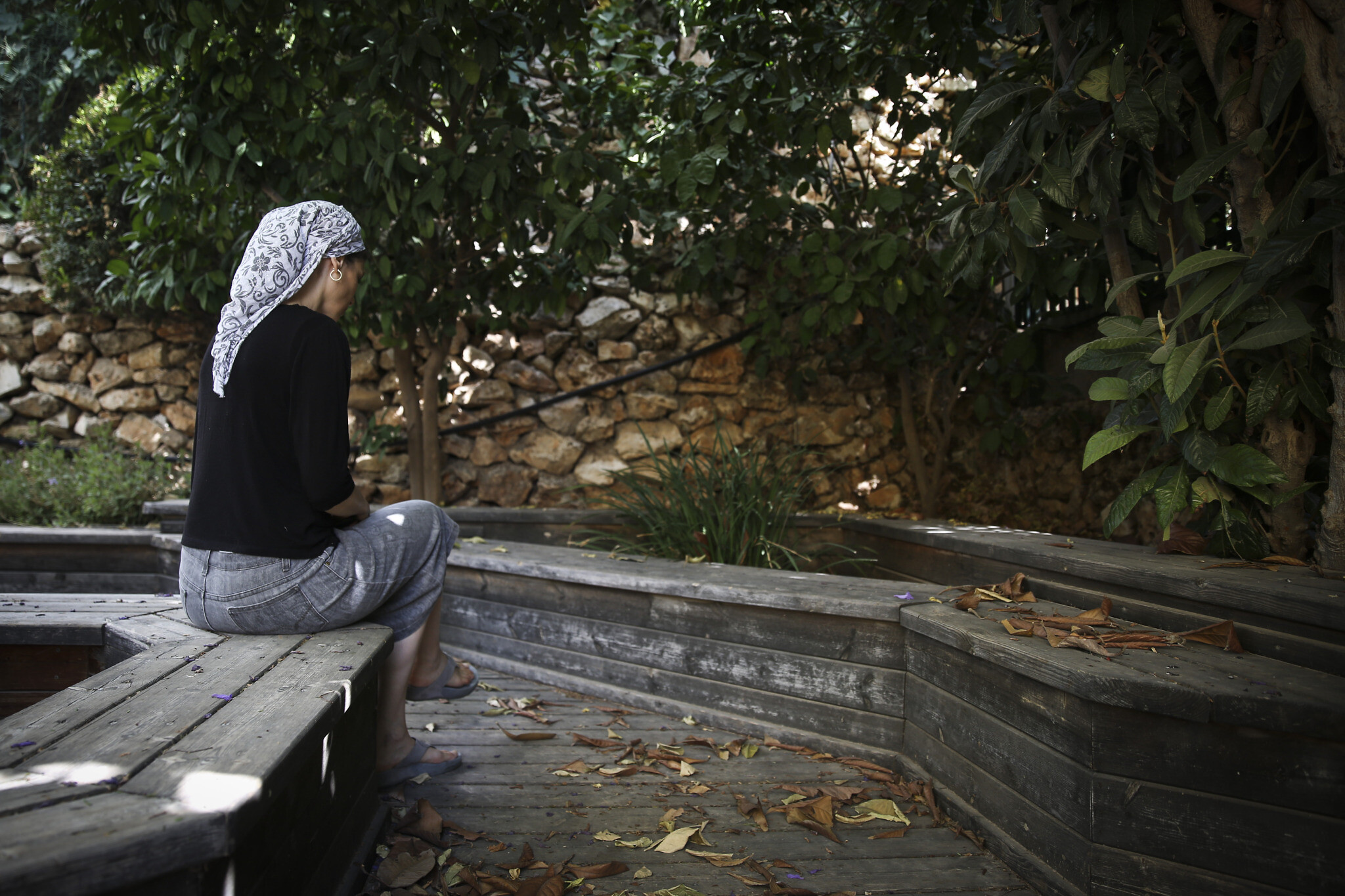 Orthodox Jewish woman sitting in a garden of a women's shelter for domestic violence