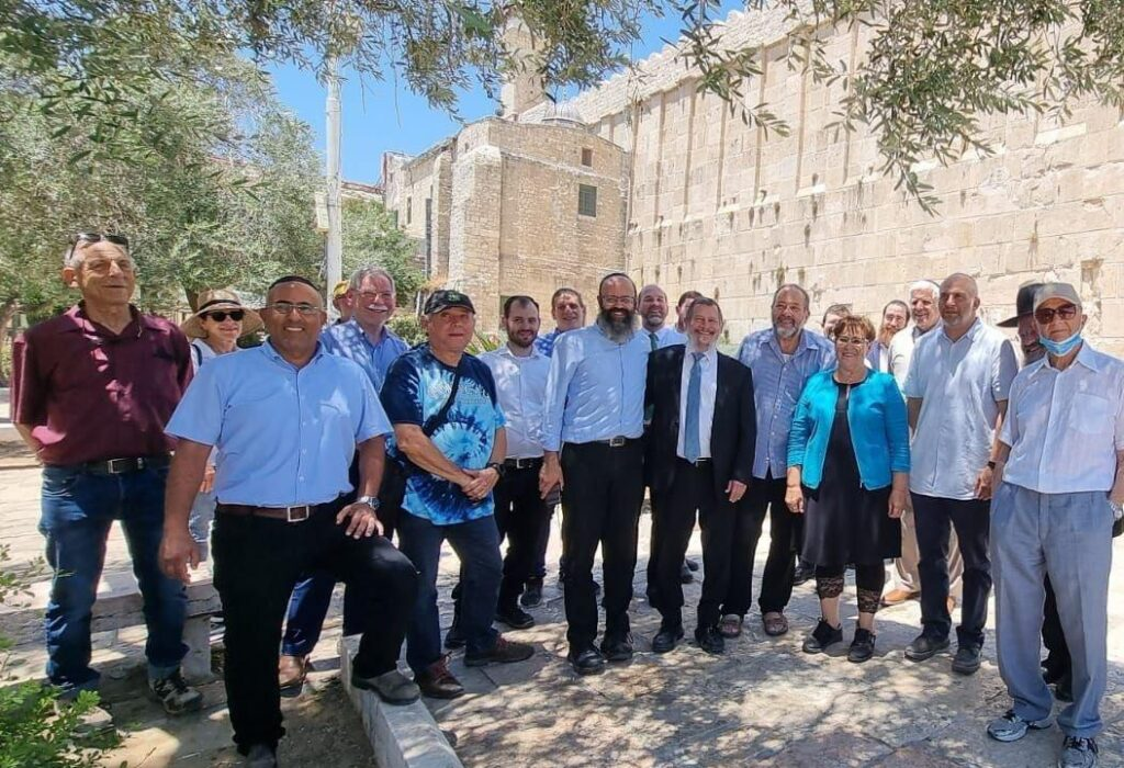 Group of Men and Women standing in the shade of a tree in front of a branch of Yad Sarah in Southern Israel
